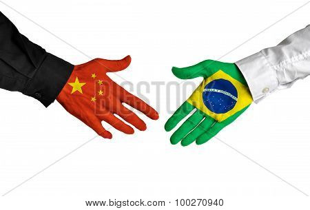 China and Brazil leaders shaking hands on a deal agreement