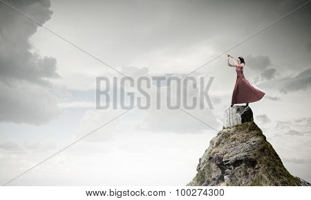Young woman in evening dress on rock playing fife