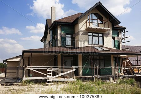 Suburban house under construction with large porch