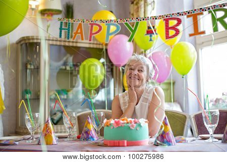 Happy elderly woman at a birthday party