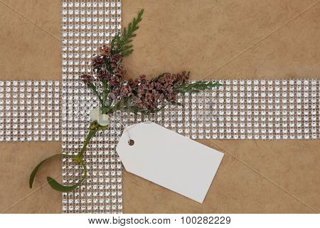 Christmas gift wrapping with diamond  ribbon, mistletoe, cedar cypress and gift tag over hemp paper background.