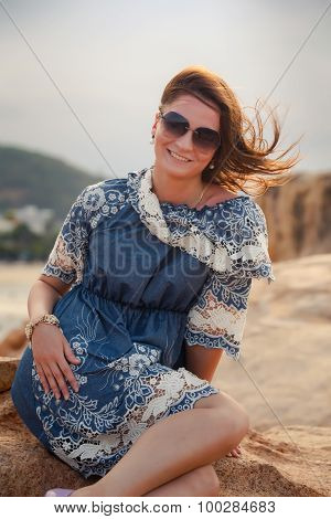 Girl In Short Grey Frock Sits On Rock Shows Legs Against City