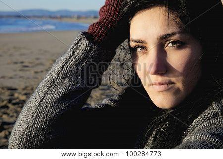 Sad Woman In Winter On Beach Looking Camera