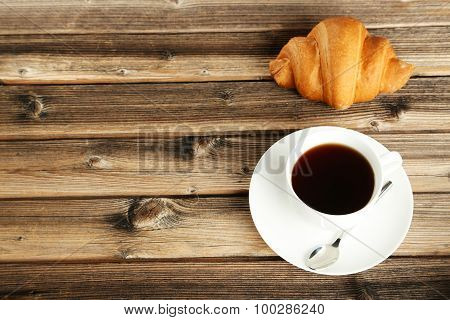Tasty Croissant With Cup Of Coffee On Brown Wooden Background