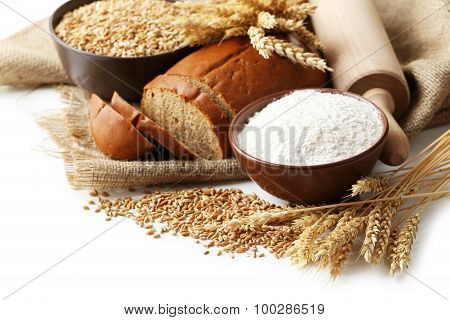 Ears Of Wheat And Bowl Of Flour And Wheat Grains On White Background