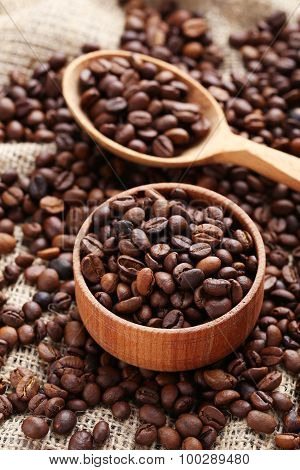 Coffee Beans In Wooden Spoon And Bowl On A Sack, Close Up