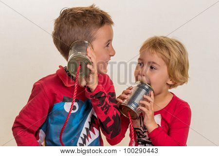 two little children with a telephone call from two cans.