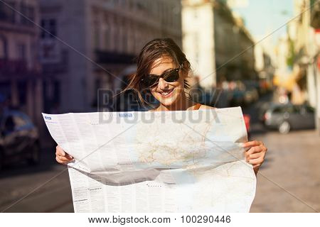 Smiling Woman Reading A Map In The Middle Of The City.