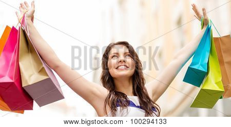 sale, shopping, tourism and happy people concept - beautiful woman with shopping bags in the ctiy