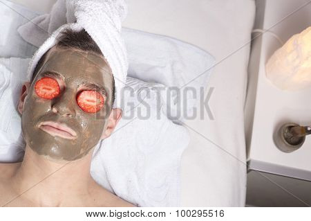 Man With A Mud Mask On This Face And Strawberry