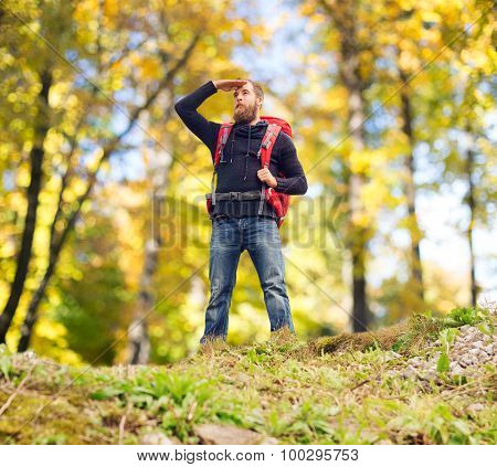 travel, tourism, hike and people concept - tourist with beard, backpack standing on edge of hill and looking far away over natural background