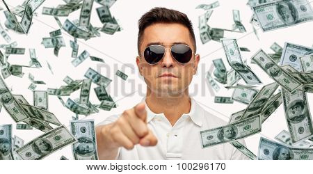 business, finance, gesture and people concept - face of middle aged latin man in sunglasses pointing finger on you with heap of falling dollar money