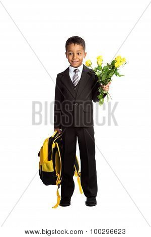 Smiling black first-grader african boy in school uniform with the backpack and bouquet of roses at his first school day