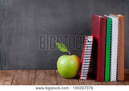 School and office supplies on classroom table in front of blackboard. View with copy space