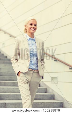 business, people and education concept - young smiling businesswoman walking down stairs outdoors