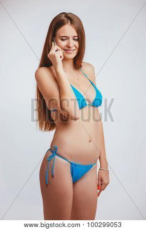 woman in a bathing suit talking phone