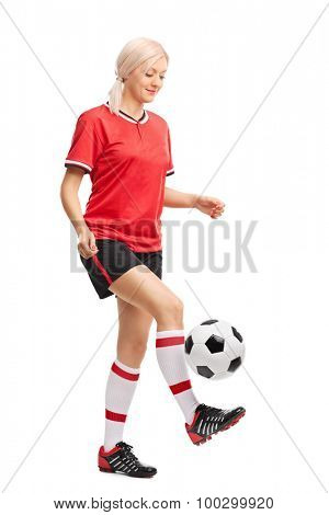 Full length portrait of a female soccer player juggling a ball and smiling isolated on white background