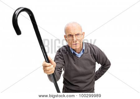 Displeased senior holding a black cane and scolding someone towards the camera isolated on white background