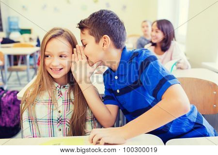 education, elementary school, learning and people concept - smiling schoolboy whispering secret to classmate ear in classroom