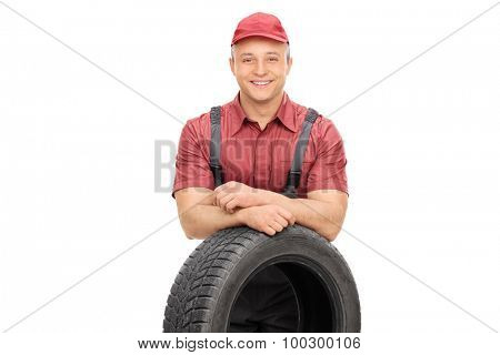 Cheerful young mechanic standing behind a car tire and looking at the camera isolated on white background