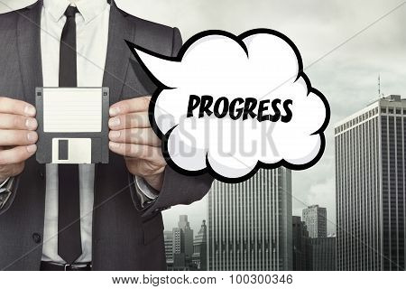 Progress text on speech bubble with businessman holding diskette