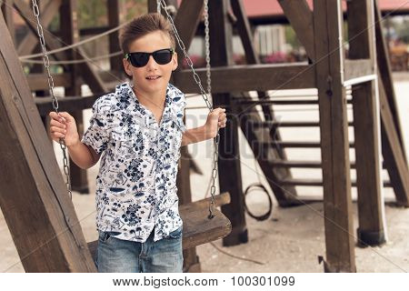 Handsome happy smiling adolescent boy in sunglasses  on a swing