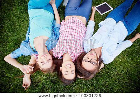 Modern teen girls in casualwear lying on green grass