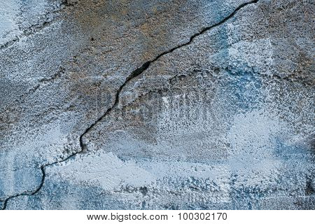 closeup of aging, grunge concrete wall texture with blue paint, cracks and chips