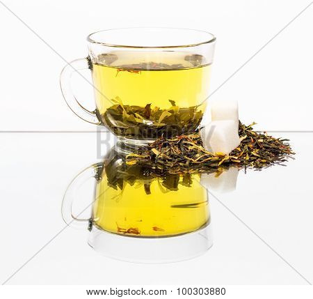 Transparent cup of tea and sugar with reflection.