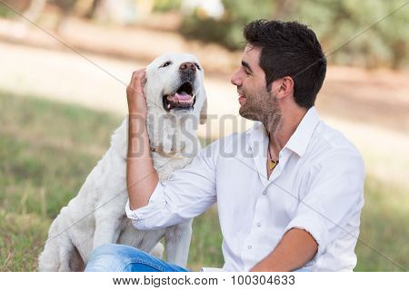 young man with old senior labrador dog in the park