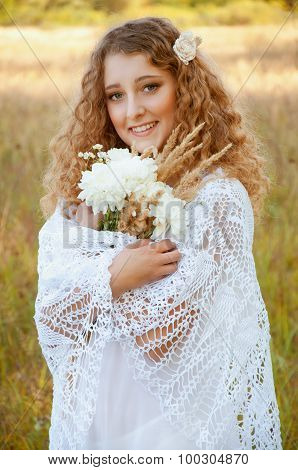 Woman With Curly Golden Hair Smiling Standing In The Field
