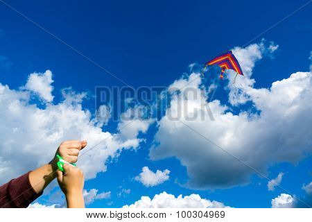 Hands holding kite in the cloudy sky. Focus to kite