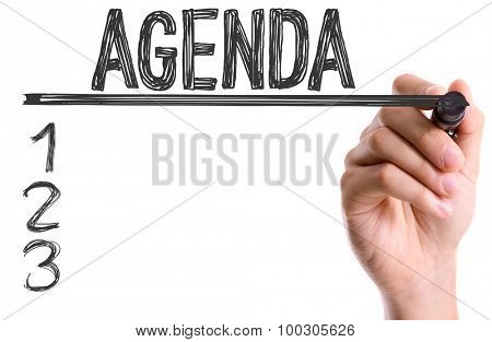 Hand with marker writing the word Agenda
