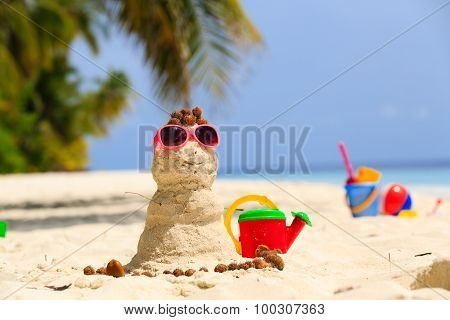Sandy snowman and toys at sand beach
