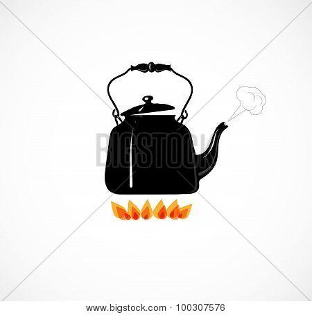 Black hot boiling kettle on fire