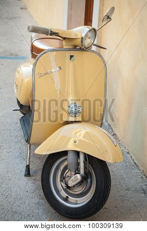 Classic Yellow Vespa Scooter Parked Near Wall