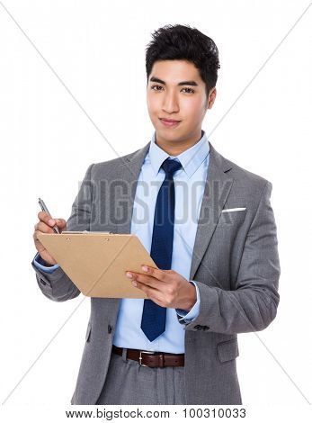 Asian young businessman take note on clipboard