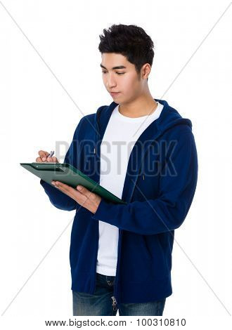 Asian young man take note on clipboard