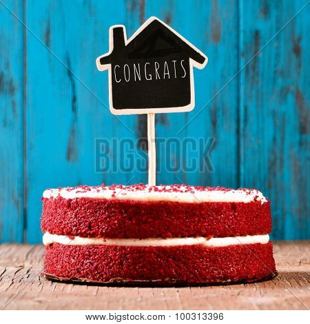 a red velvet cake with a chalkboard in the shape of a house with the text congrats, on a rustic blue wooden surface, with a retro effect