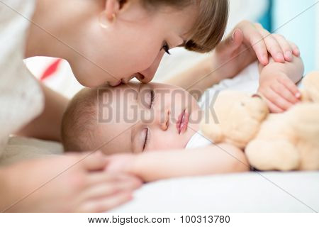 Closeup on mother kissing sleeping baby