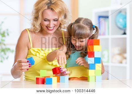 child and mom playing wooden toys at home