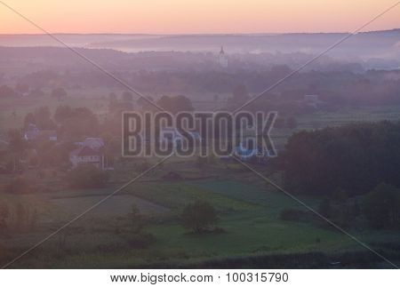 Morning fog over the river in the village. View from the hill. Ukraine, Europe