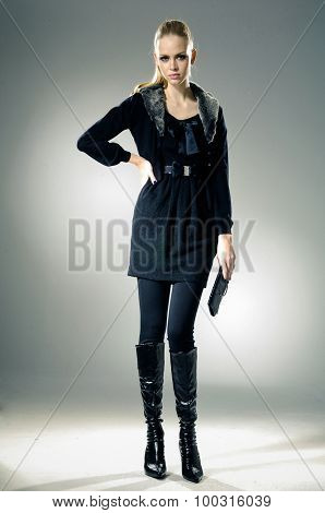 Full body High fashion model holding little purse posing on light background