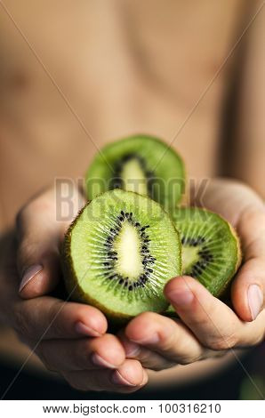 Sliced Kiwi in the boy handle selective focus toned picture
