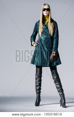 full-length fashion model in coat clothes posing on light background