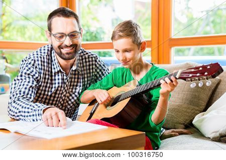 Father and son playing guitar at home, making music together