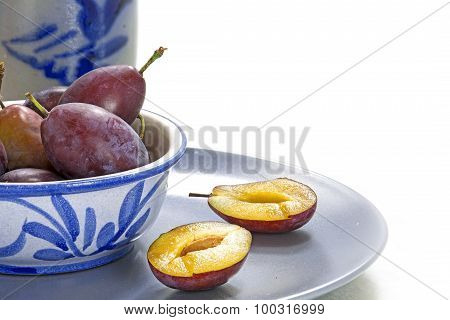 Plums In Blue Crockery, One Of Them Is Cut, White Background