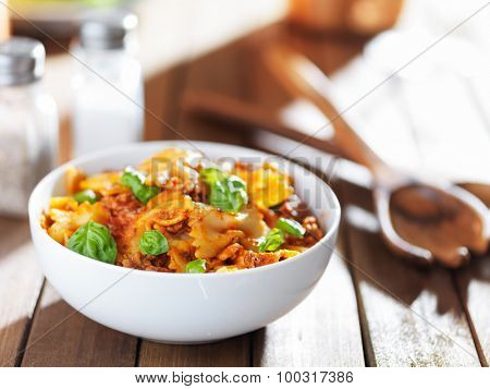 bowl of farfalle bowtie pasta with beef, basil leaves and tomato sauce