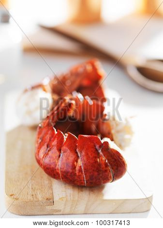 three cooked lobster tails laid on on wooden cutting board during preparation