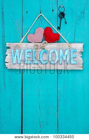 Welcome sign with hearts and keys hanging on rustic door